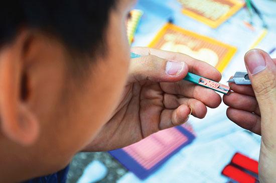 Đôi tay khéo léo đang khắc chữ trên thân cây bút chì.
