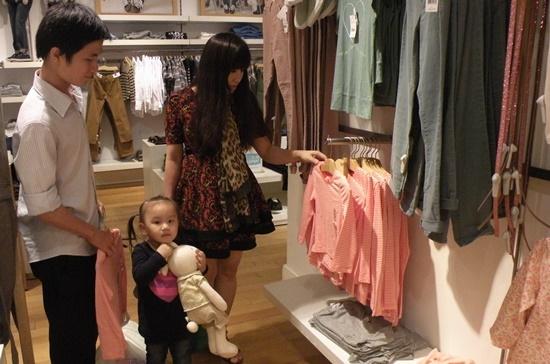 Phụ huynh chọn đồ cho con tại cửa hàng Gap ở Trung tâm thương mại Vincom. Ảnh: Vũ Yến