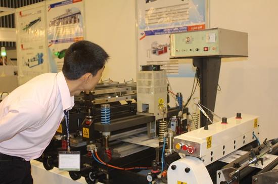 Khách tham quan đang xem hoạt động của một máy ép nhựa thế hệ mới tại VietnamPlas 2014.