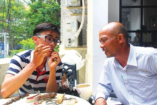 Nghệ nhân đàn môi trẻ tuổi Đặng Văn Khai Nguyên đang nói về đàn môi cho một vị khách.