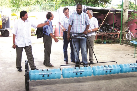 Ông Thắng (bìa trái) đang giới thiệu về máy sạ lúa cho các nhà khoa học nước ngoài.