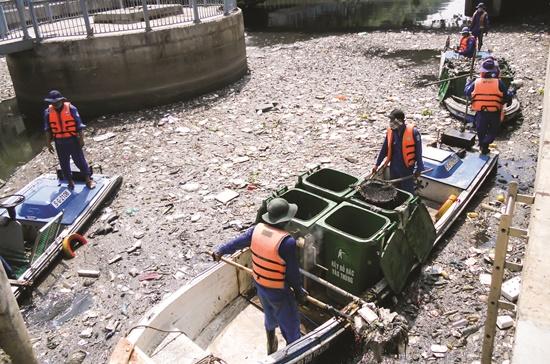Công nhân đang vớt rác trên dòng kênh Nhiêu Lộc-Thị Nghè. Ảnh: Văn Nam