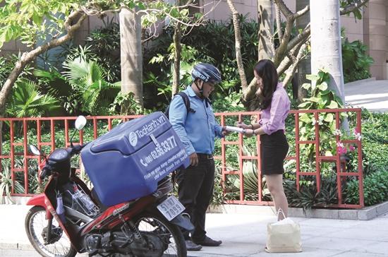 Nhân viên tochanh.vn đang giao hàng cho khách hàng.  Ảnh: Thành Hoa