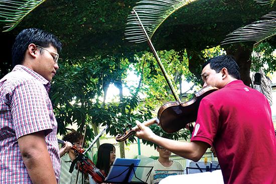 Anh Lê Ngọc Tú (phải) đang hướng dẫn cách đánh violin cho một bạn trong nhóm.