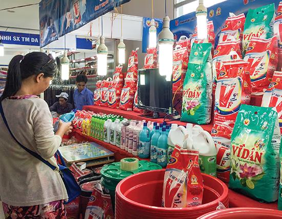Người tiêu dùng tham khảo giá sản phẩm tại một hội chợ khuyến mãi.